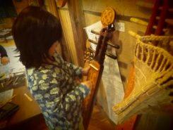トンコリ(樺太アイヌの五弦楽器/人の形をしている)を弾く少女