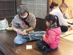 糸の先をコマにかけてコマを回すと糸がつむげる。力の調節が難しい