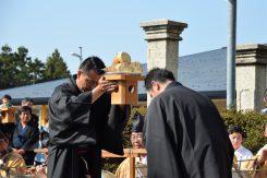 神輿の中で鎮座する神様へ春の収穫を感謝しお供えを順番に手渡していく