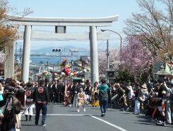 鳥居をくぐり行進がスタート。後ろは琵琶湖