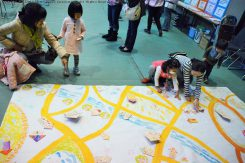 「近江八幡子育てネットワーク」さんのコーナーでは、みんなで街づくり。プレイコーナーで作った木の板のお家を並べて楽しい街が出来上がっていく!