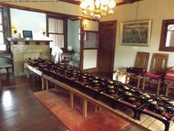 旧伊庭家の居間。普段ある大テーブルは片づけられ、御膳が並べられていた