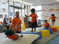 マットで前転。少し勾配をつけて回転しやすくし、子どもたちが達成感を持てるように工夫している